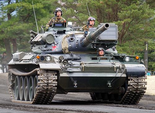 74式戦車。戦車に乗る時は車内で座るより砲塔上に寄りかかるほうが快適かも。全長:9410mm、重量:38t、最高速度:53km/h、乗員:4名