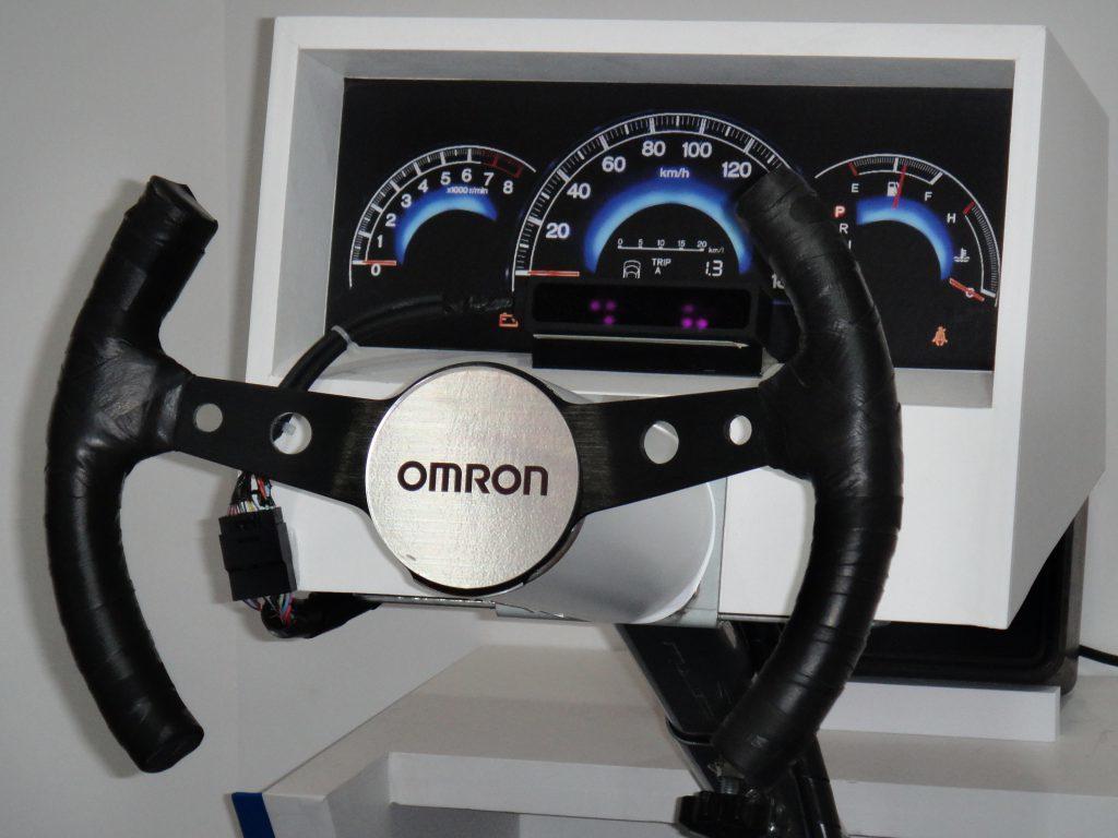 オムロンのステアリング上部、スピードメーターの下に設置されているものが、認識用のカメラ