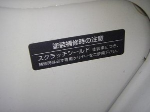 スクラッチシールド塗装が施された日産車に必ずついている注意表記。補修時には専用クリヤーが必須となる。